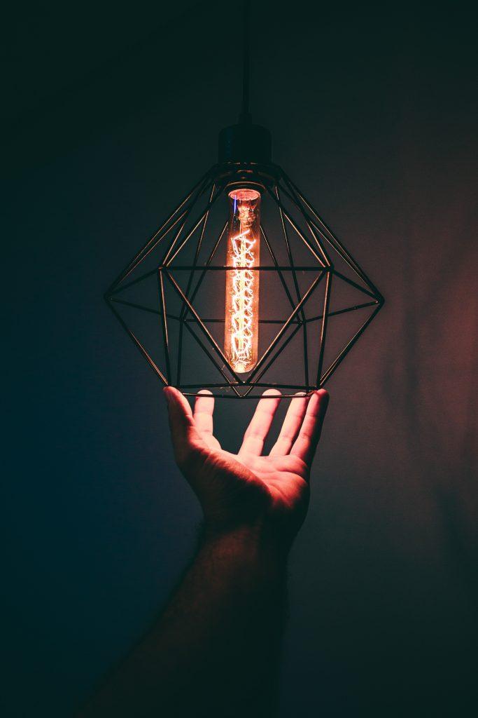 person-holding-pendant-light-973506